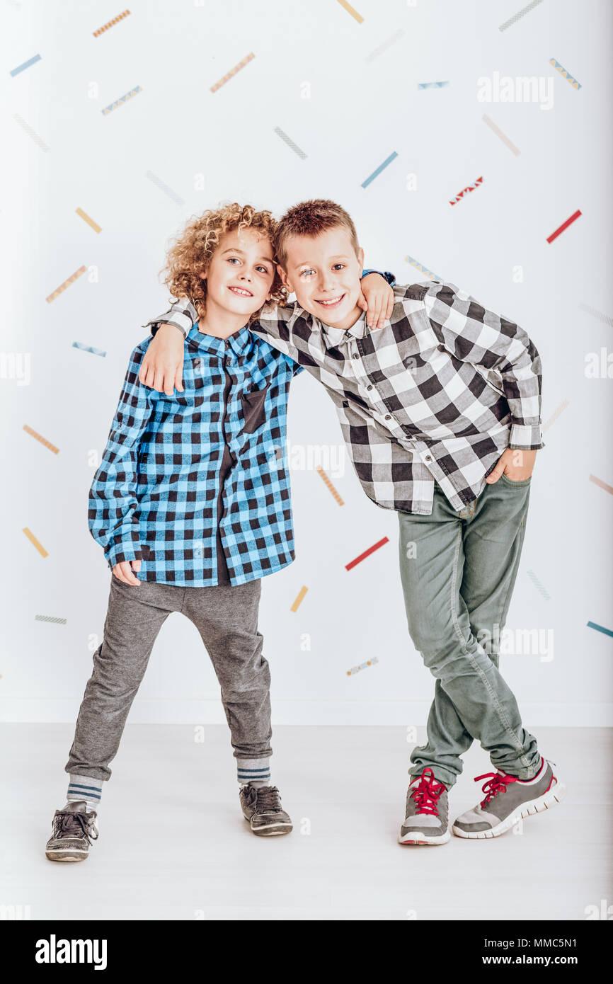 Dos muchachos jóvenes felices de pie y abrazando a cada uno de los otros Imagen De Stock
