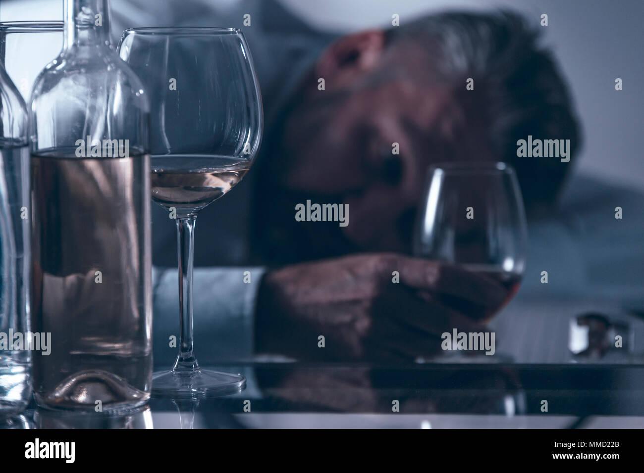 Close-up de un borracho desesperado hombre de mediana edad inclinarse sobre la mesa detrás de botellas y vasos con alcohol Imagen De Stock