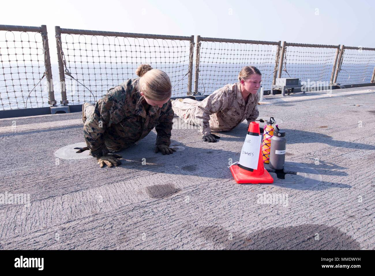 171019-N-UK248-058 5ª Flota de EE.UU. ZONA DE OPERACIONES (Oct. 19, 2017) Marine Cpl. Caitlin McCoy (derecha), un nativo de Plymouth, Massachusetts y Lance Cpl. Fe Swoverland, un nativo en Mishawaka, Indiana, ambos asignados a la 15ª Unidad Expedicionaria de los Infantes de Marina (MEU) a bordo de la nave de aterrizaje dock anfibio USS Pearl Harbor (LSD 52), practicar buceo pushups bombardero durante el Marine Corps Martial Arts Program (MCMAP) de entrenamiento de circuito en la cubierta de vuelo del buque. Pearl Harbor es parte de la América Amphibious Ready Group (ARG) y, con la 15ª MEU, embarcado está desplegado en apoyo de la seguridad marítima opera Imagen De Stock