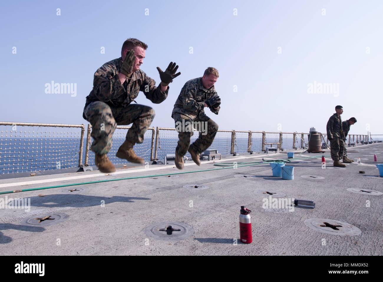 171019-N-UK248-047 5ª Flota de EE.UU. ZONA DE OPERACIONES (Oct. 19, 2017) Marine Cpl. Andrew Pittman, de izquierda, de color gris, Ga., y Lance Cpl. Chris Watkins, de Berea, Ky., ambos asignados a la 15ª Unidad Expedicionaria de los Infantes de Marina (15 MEU) a bordo de la nave de aterrizaje dock anfibio USS Pearl Harbor (LSD 52), participar en el Marine Corps Martial Arts Program (MCMAP) de entrenamiento de circuito en la cubierta de vuelo del buque. Pearl Harbor es parte de la América Amphibious Ready Group (ARG) y, con la 15ª MEU, embarcado está desplegado en apoyo de operaciones de seguridad marítima y seguridad teatro en los esfuerzos de cooperación en U Imagen De Stock