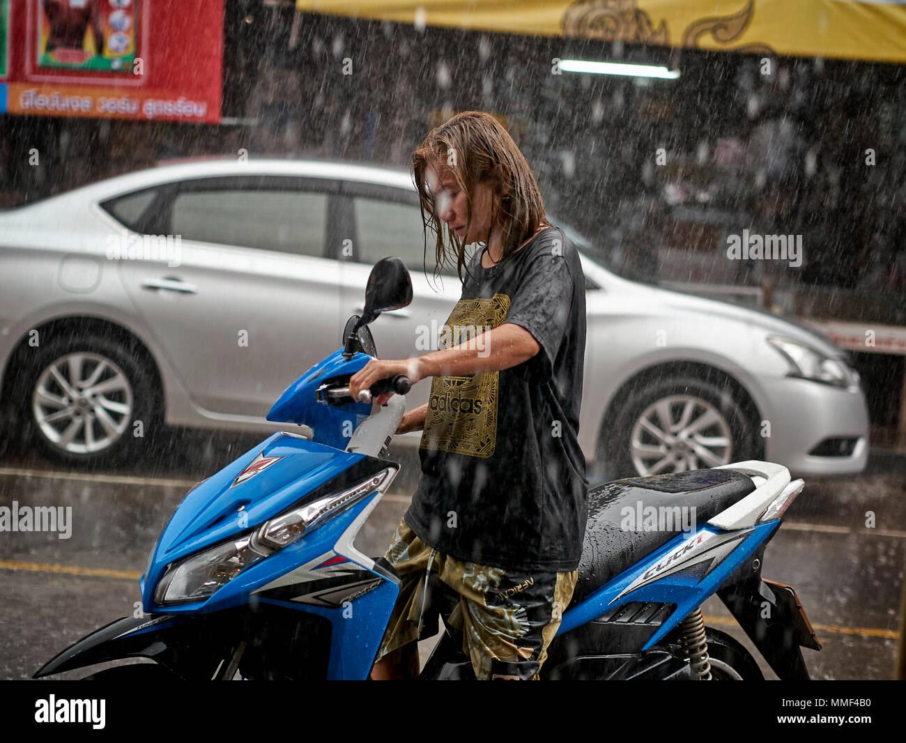 La lluvia. Mujer con moto capturados en lluvias torrenciales. Tailandia la temporada de los monzones. El sudeste de Asia. Imagen De Stock