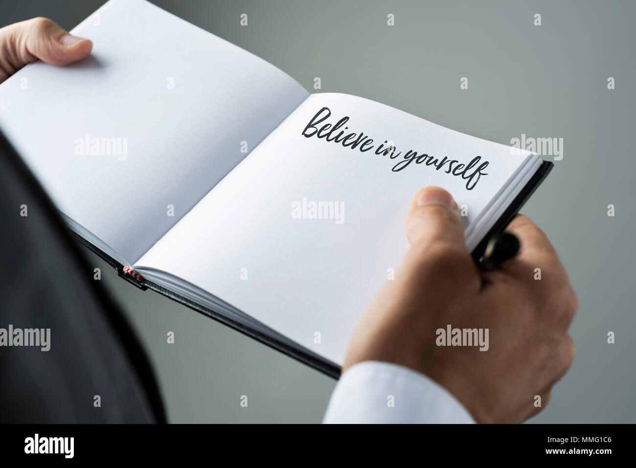 Primer plano de un joven hombre caucásico en un elegante traje con un portátil en sus manos con el texto creer en ti mismo escrito en él Imagen De Stock