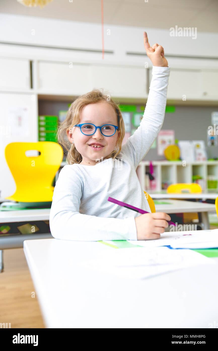 En la escuela - Feliz levantando la mano en el aula escolar Imagen De Stock