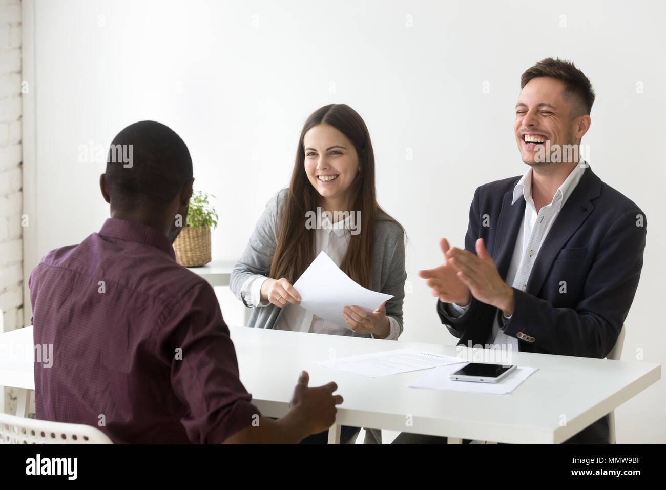 Candidatos africanos hacen reír hr en una entrevista de trabajo, buena impressio Imagen De Stock