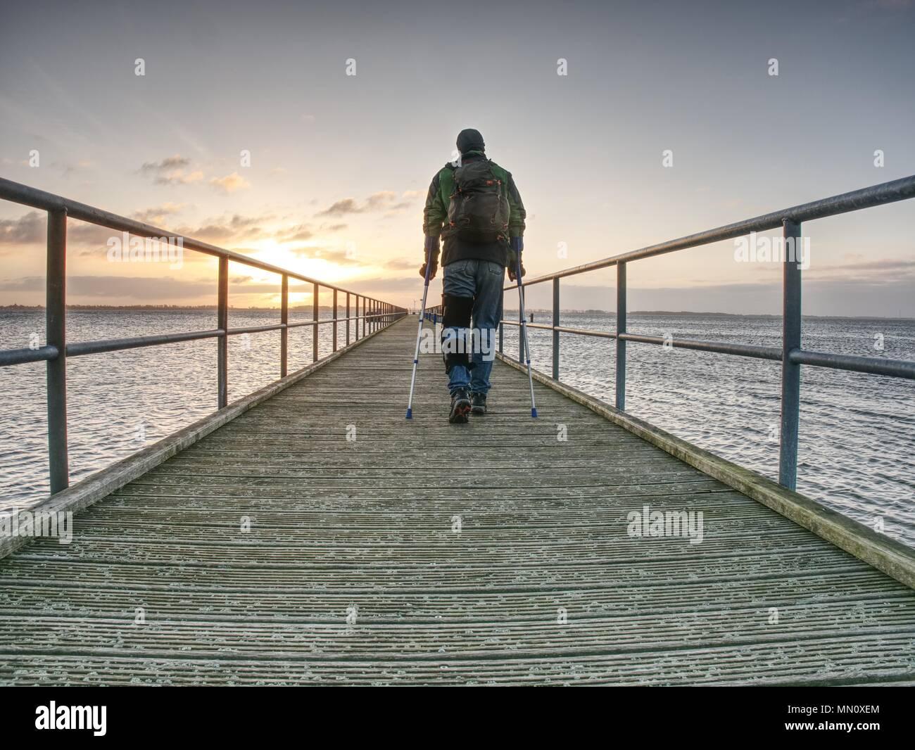 El hombre herido con chaqueta con capucha y muletas antebrazo mirando tristemente en agua de mar. Soporte Traveler en puente marítimo dentro de mañana y pensar. Nostálgicos Imagen De Stock