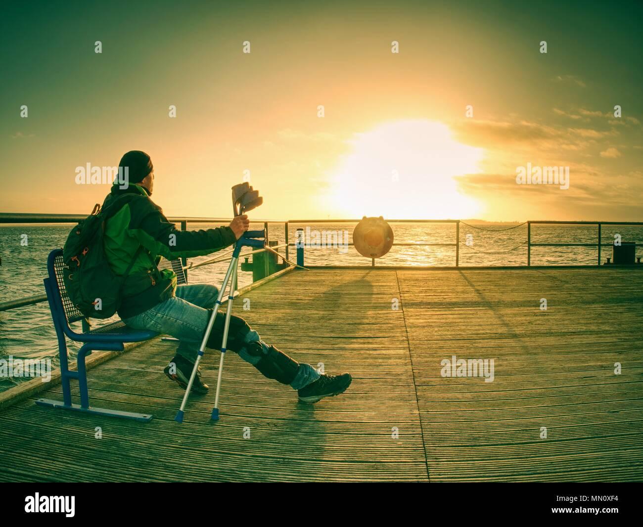 Sombría silueta nostálgica de triste melancólico solitario hombre adulto con chaqueta con capucha parado sobre el puente del lago dentro de madrugada y pensando Imagen De Stock