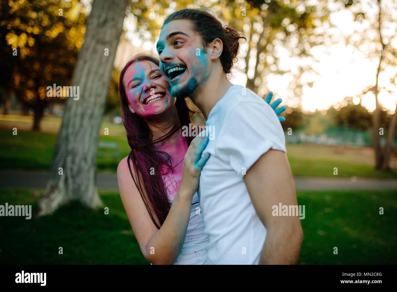 Pareja joven sonriente con polvo coloreado untado en sus rostros. Alegre al hombre y a la mujer disfrutar festival de colores al aire libre en el parque. Foto de stock