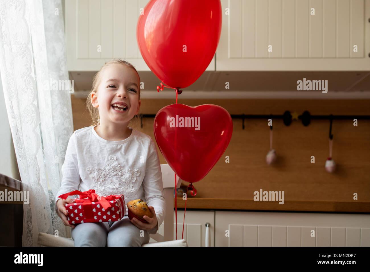 Lindo niño niña celebrando el 6º cumpleaños. Chica sujetando su cumpleaños cupcake y bellamente envuelto presente, sentado rodeado de globos. Imagen De Stock