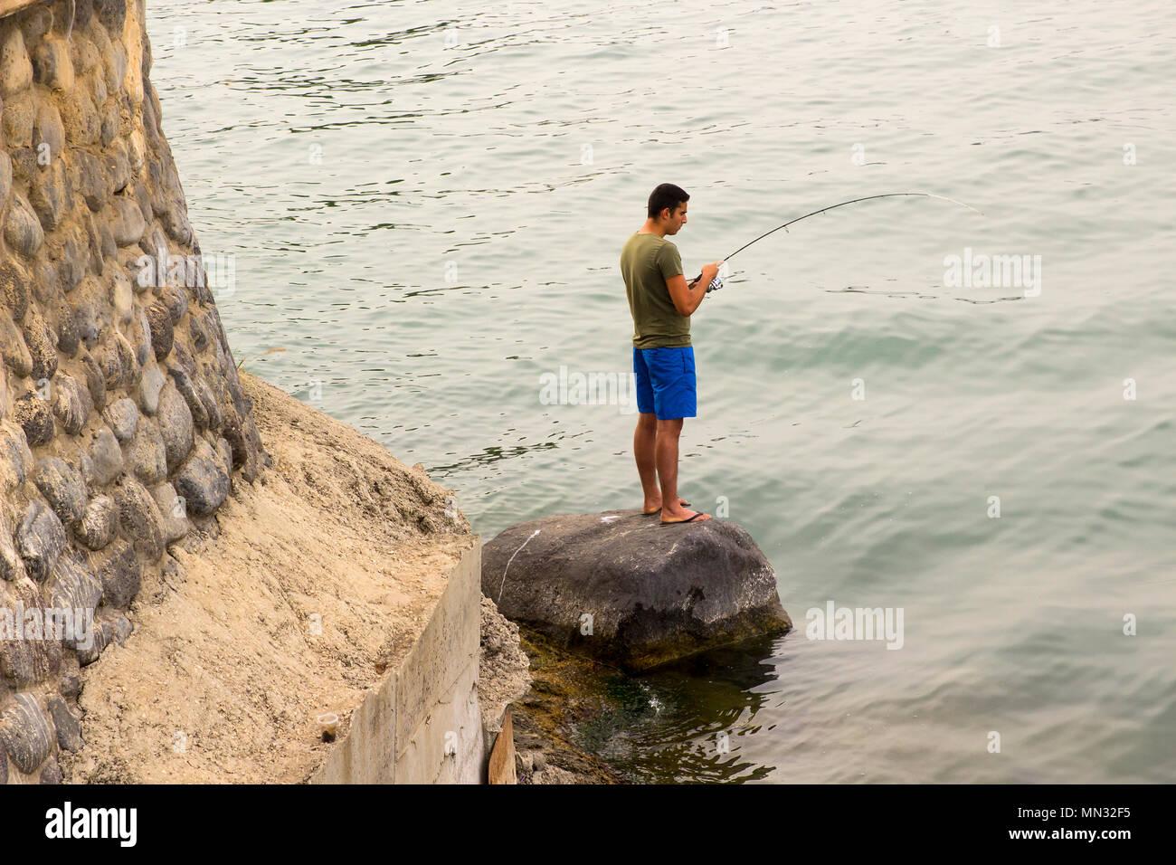 6 de mayo de 2018 Tiberíades en el Mar de Galilea, Israel. Un joven se levanta con orgullo un pez que ha capturado con una spinning y spinner. Imagen De Stock