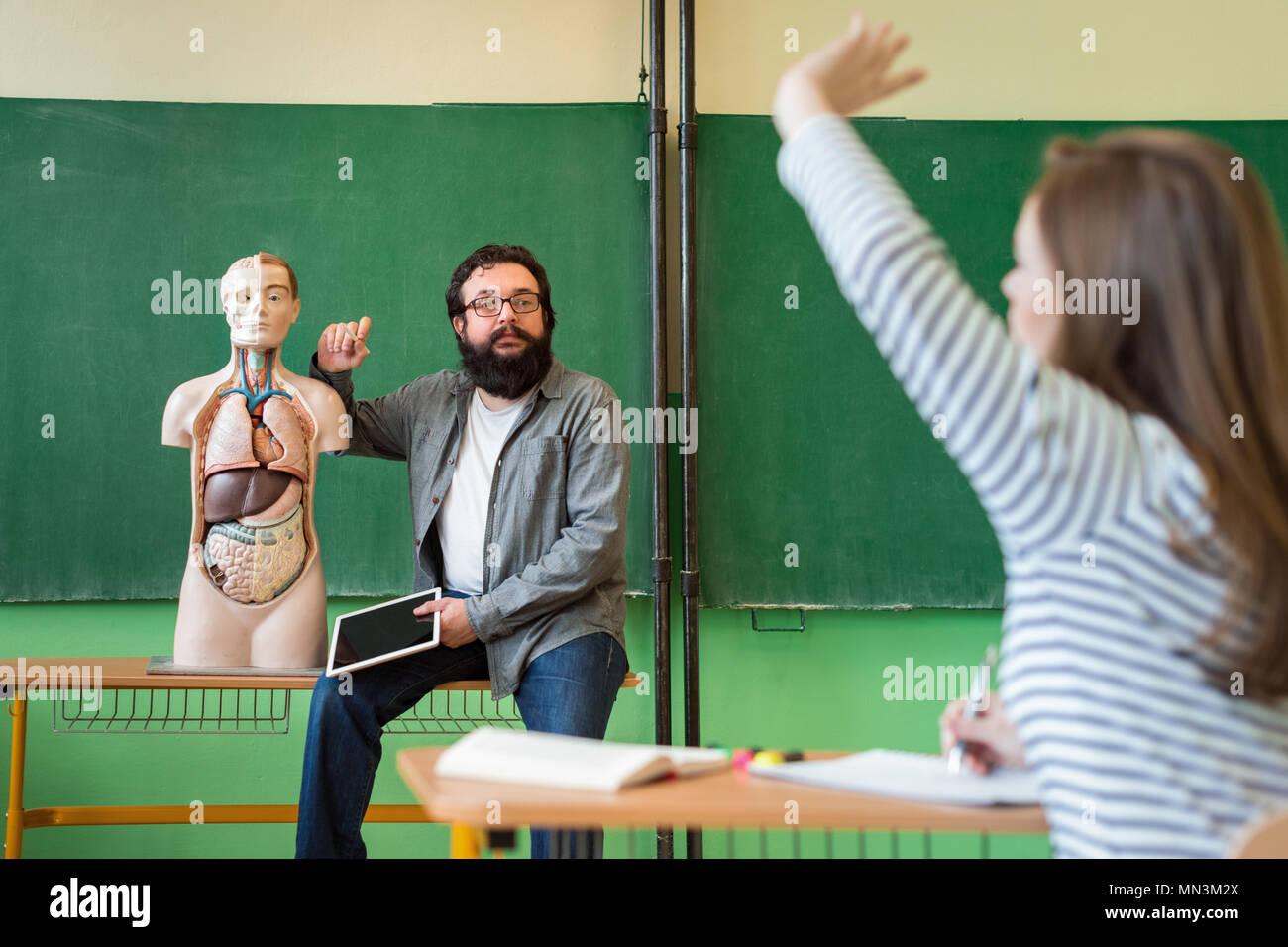 Macho joven profesores hispanos en clase de biología, sosteniendo digital y tableta enseñar anatomía del cuerpo humano, utilizando modelos artificiales en el cuerpo. Imagen De Stock