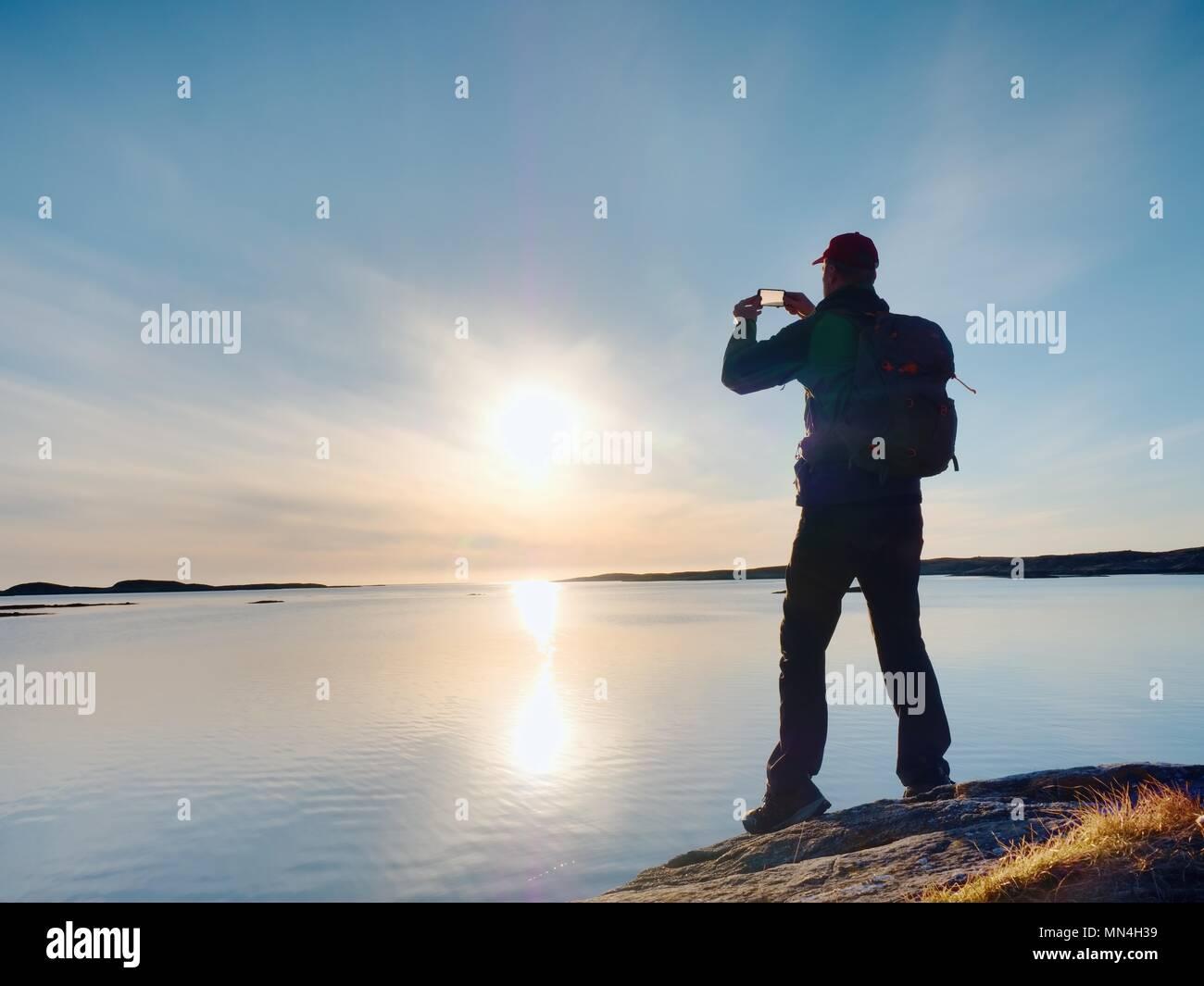 Silueta de hombre conservar recuerdos con la cámara del teléfono en su mano. Maravillosa puesta de sol en el mar, buen nivel de agua Imagen De Stock