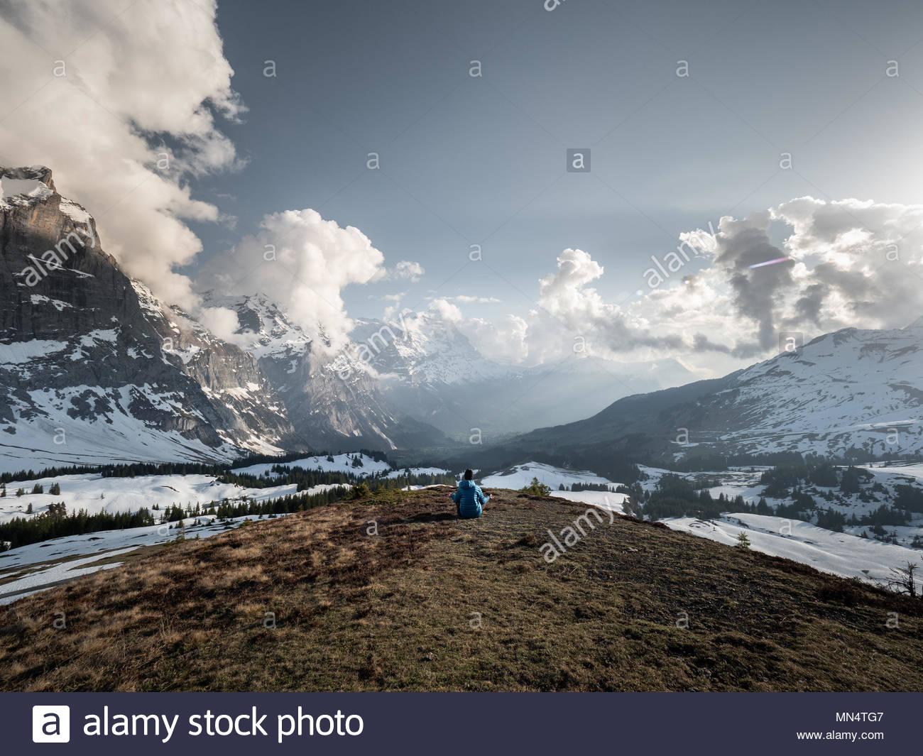 Un hombre meditando en wide open paisaje de montaña en frente de los grandes picos de montaña de los alpes suizos y montañas Eiger, en conceptos como la relajación, sana l Imagen De Stock