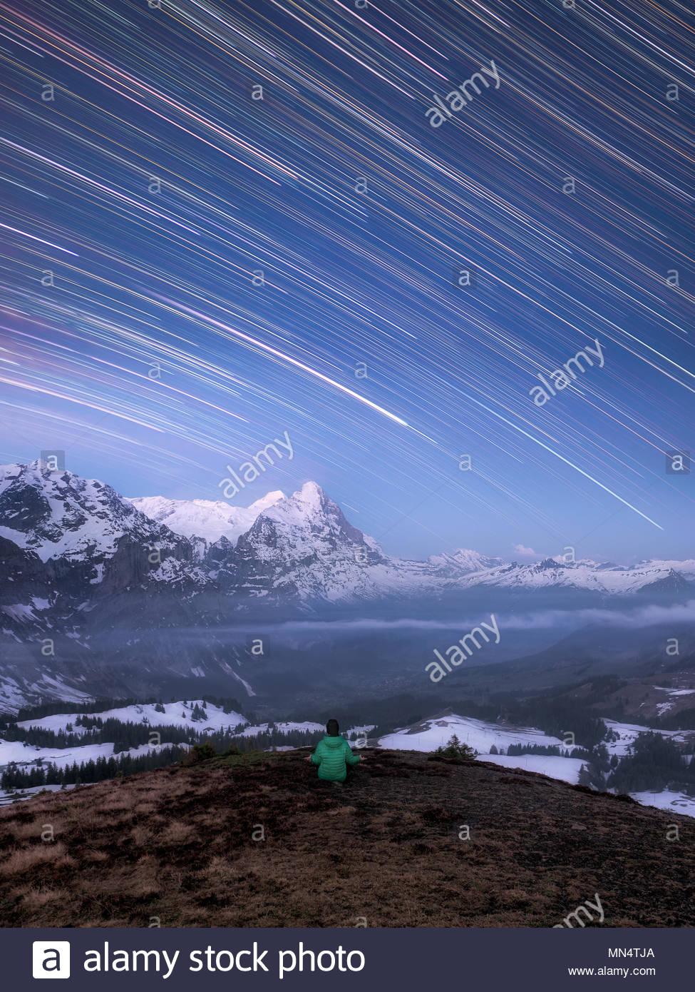 Un hombre sentado bajo el cielo nocturno en las montañas meditando, shooting star como estelas de estrellas de la rotación de la tierra y cubiertos de nieve, paisaje alpino Imagen De Stock