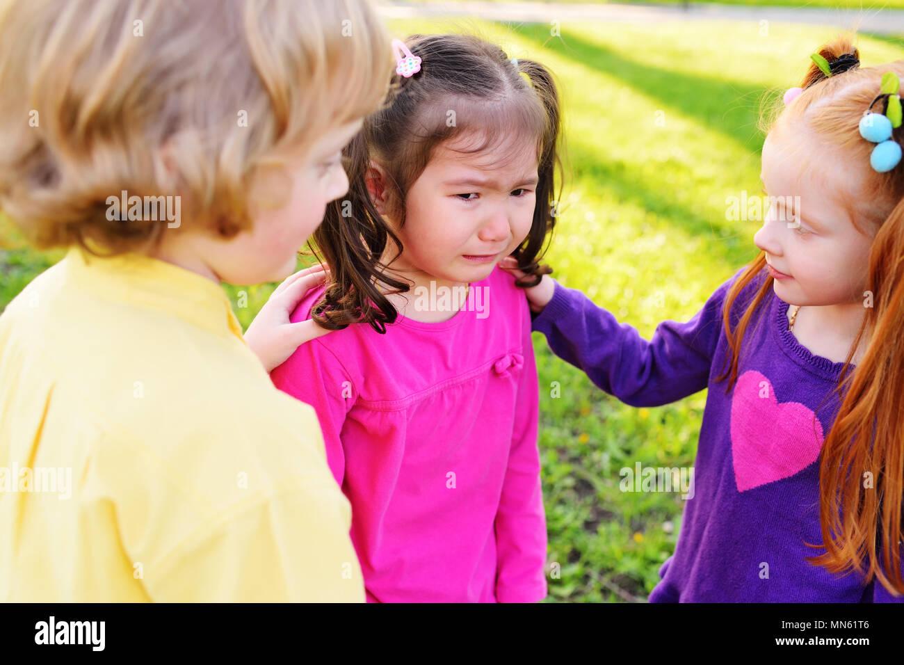 Los niños sienten compasión por una niña llorando. Imagen De Stock