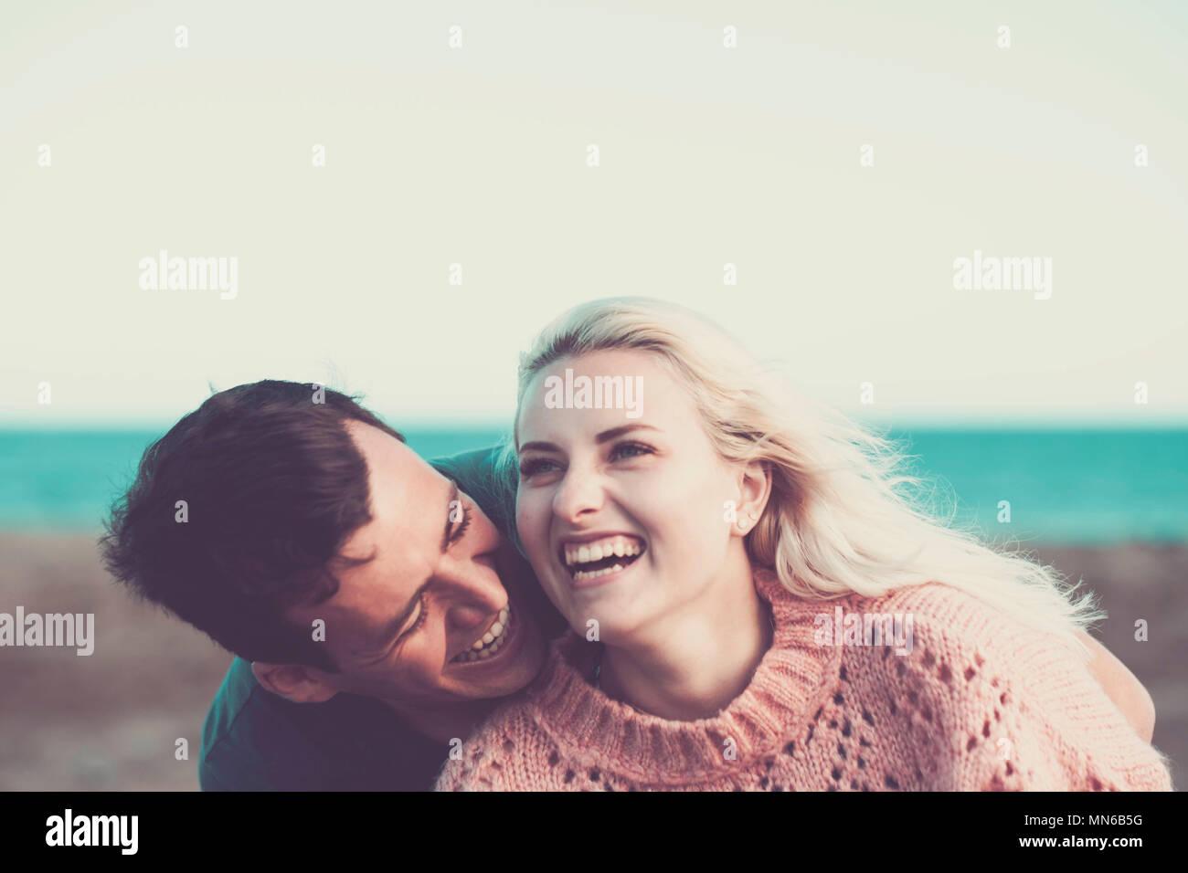 Joven pareja caucásica rubia y cabello negro permanecer juntos con alegría y con amor exterior con la playa y el océano en el fondo. vacaciones concepto con Imagen De Stock