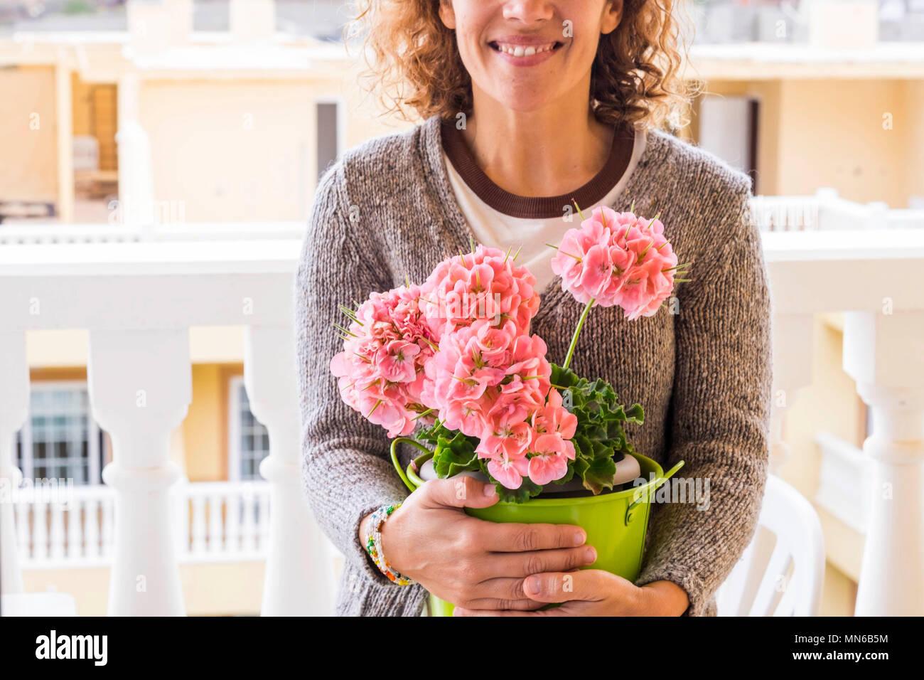 Hermosa mujer caucásica edad media sonrisa y proteger sus flores teniendo cuidado de ellos con un abrazo. terraza en casa escena con colores de sprin Imagen De Stock