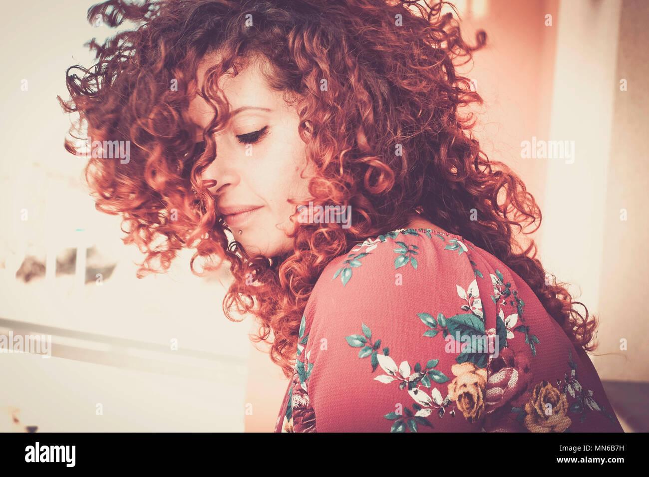 Bonito color rojo retrato de una niña de pelo rojo perdido en sus pensamientos solo en casa. cálidos colores y tonos, los ojos cerrados y solitarios, hermosa joven cacuasian woma Imagen De Stock
