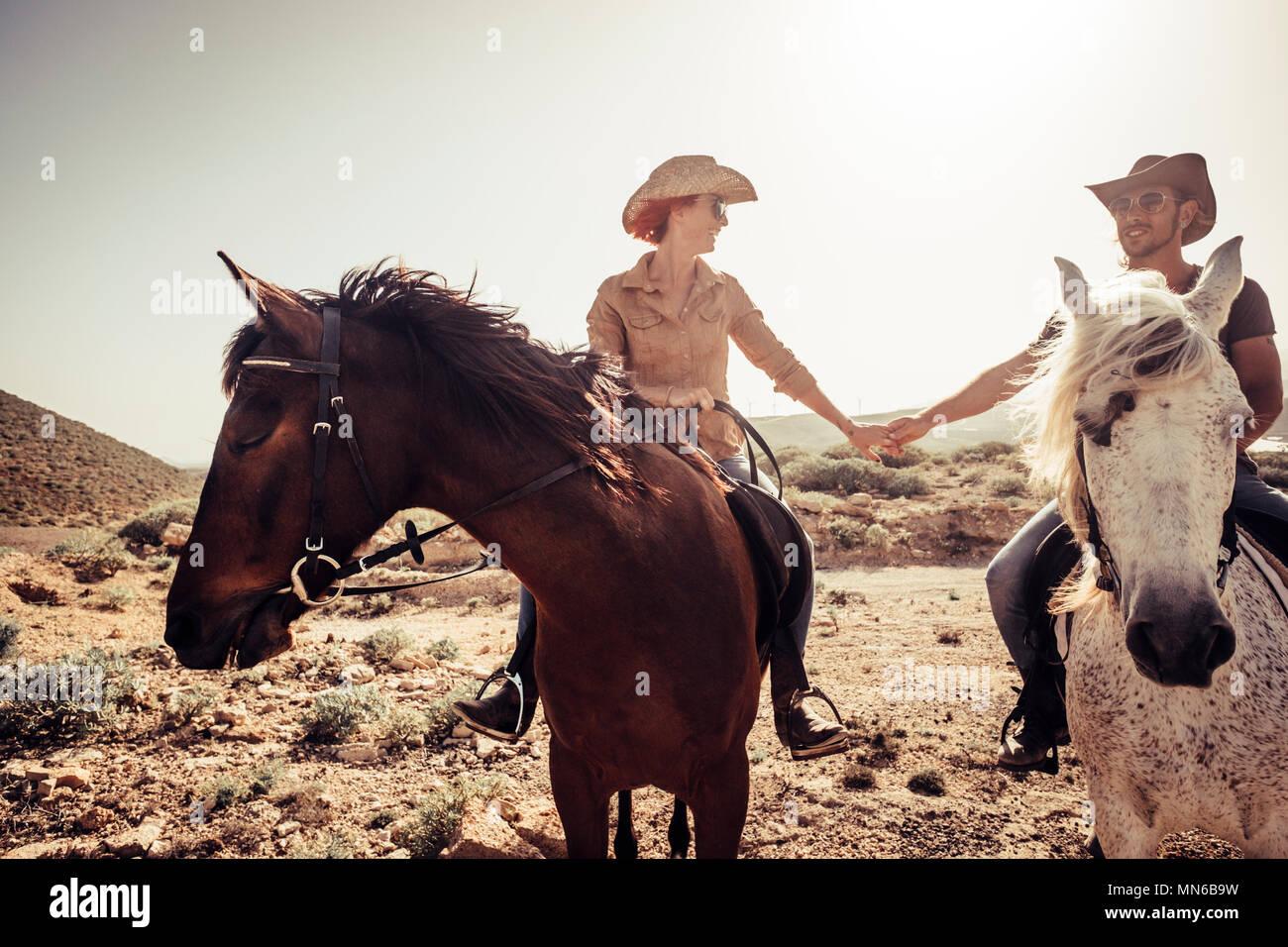 El amor y la amistad entre la mujer y el hombre joven y bella como vaquero moderno viviendo una alternativa de vida en contacto con la naturaleza y el caballo Imagen De Stock