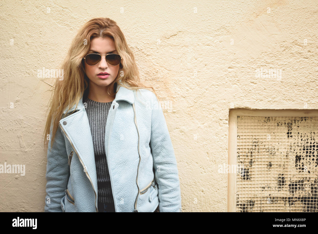 88eaa7b43 Retrato de joven y bella mujer rubia con el pelo rizado. Vestida de chaqueta  de cuero