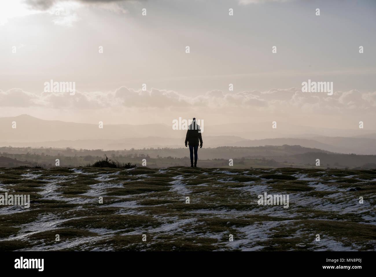 Una solitaria mujer de pie en la parte inferior de heno Bluff en la Montaña Negra viendo la tarde luz sobre Herefordshire Foto de stock