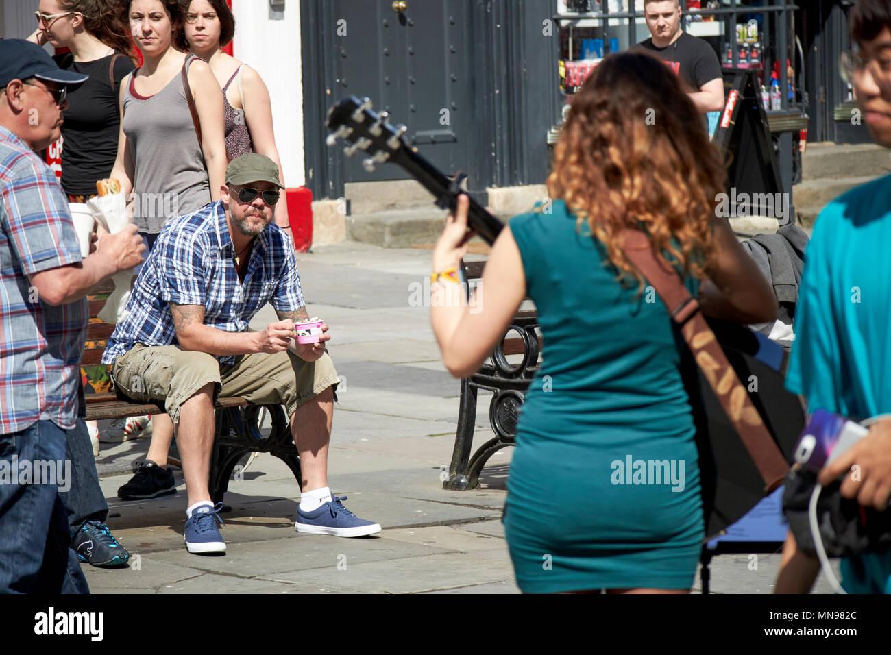 Macho y hembra de turista se sienta relojes músico callejero jugar en el sol en el patio de la abadía de Bath Inglaterra Imagen De Stock