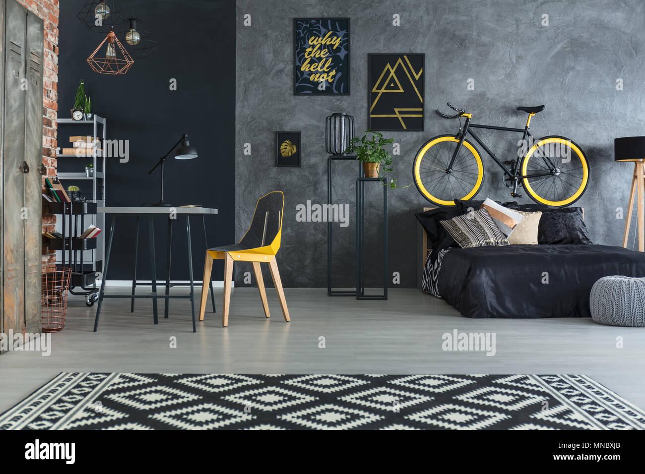 Hipster dormitorio con cama, escritorio, silla y pared de ladrillo Imagen De Stock
