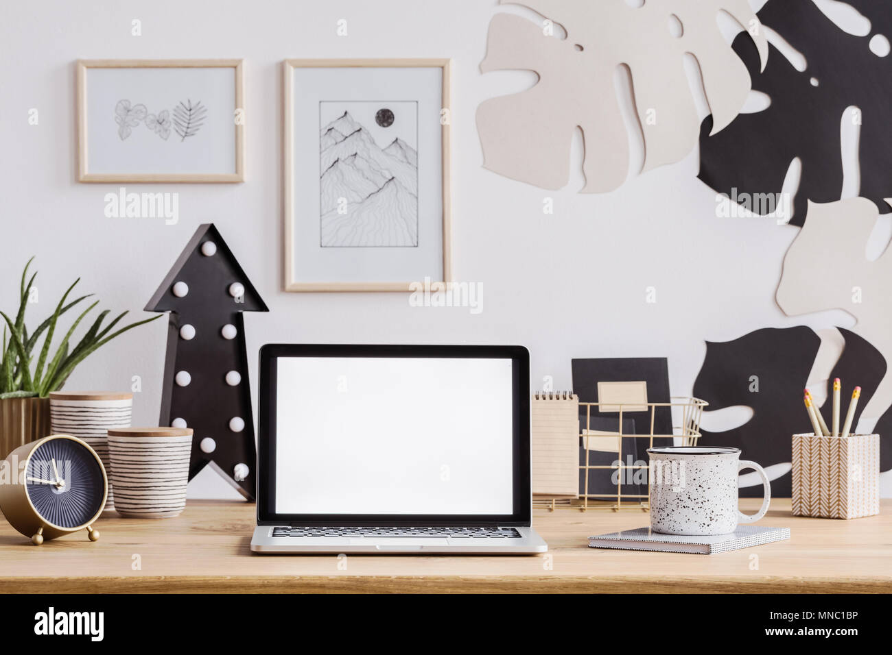 Portátil con pantalla blanca sobre un mostrador de madera con reloj, taza y lápices así como decoraciones de pared Foto de stock