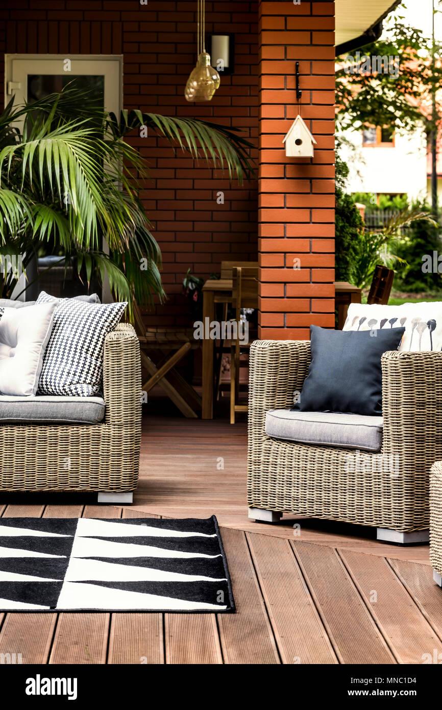 Terraza de madera de una casa de verano, con cómodos sillones y sofás de ratán Foto de stock