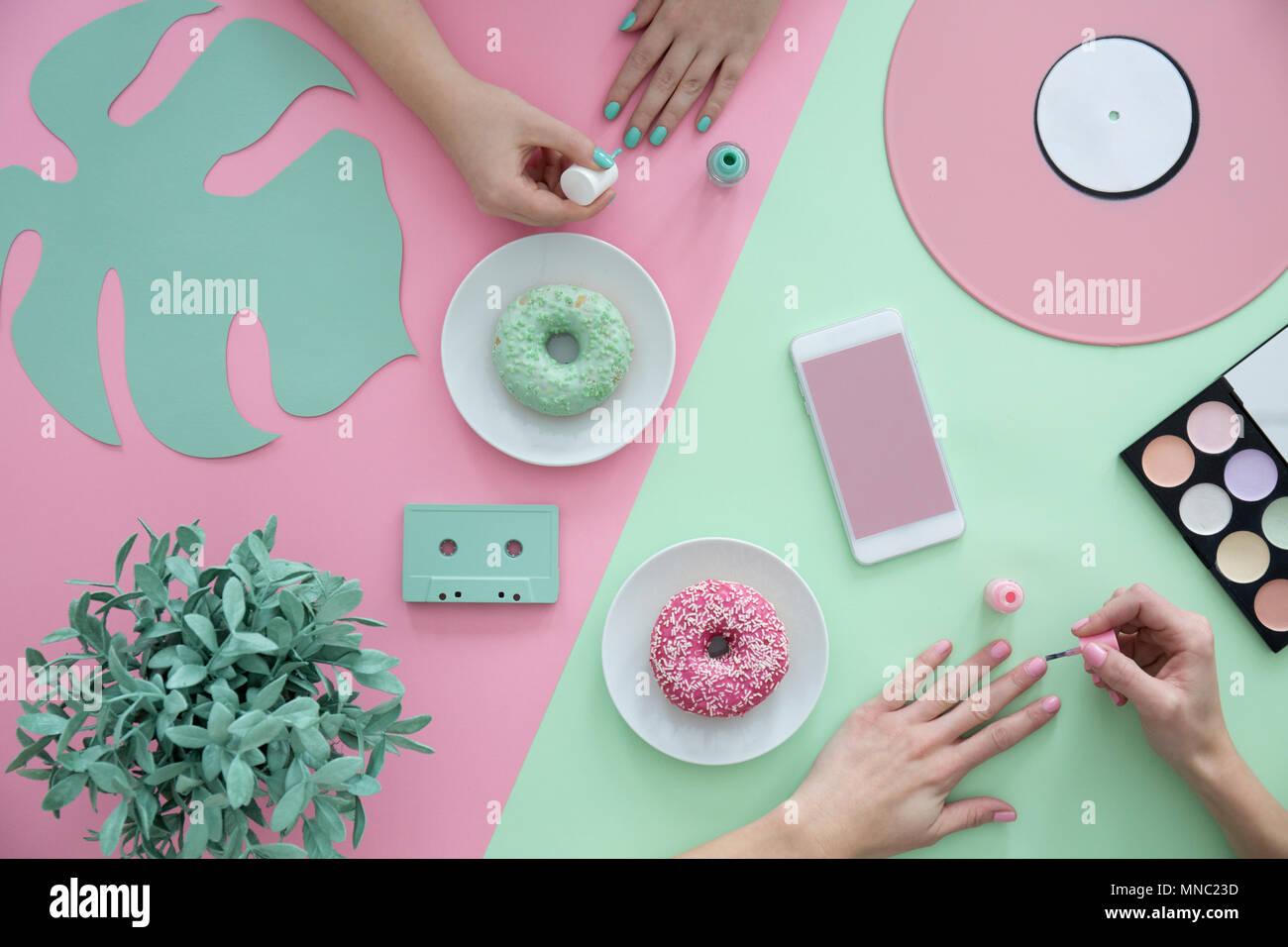 Las niñas pintar uñas sobre una mesa verde y rosa con buñuelos y ...