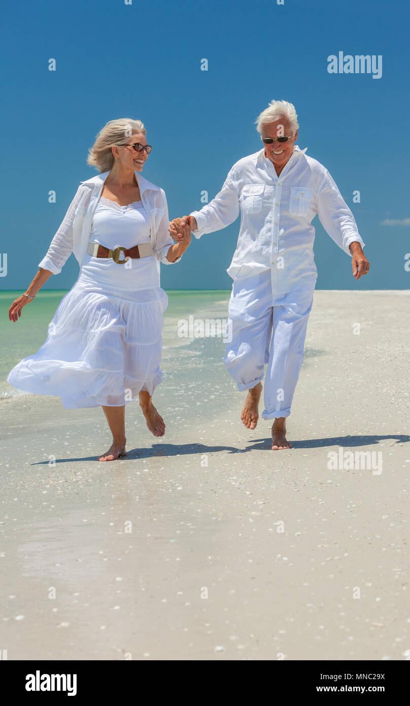 Feliz senior hombre y mujer pareja de jubilados con gafas de sol tomados de  la mano 80dc26fca05e