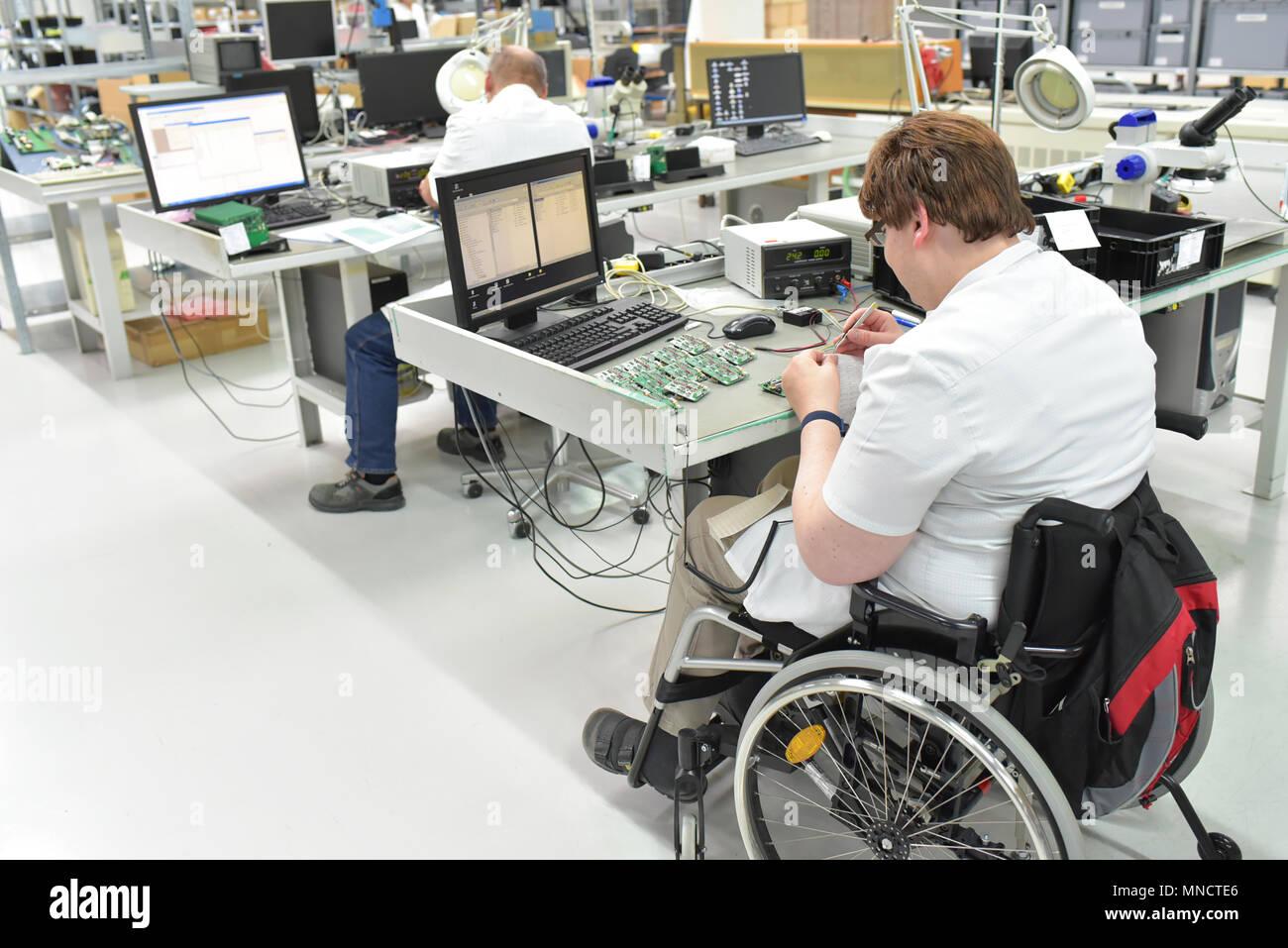 Los trabajadores discapacitados en silla de ruedas Montaje de componentes electrónicos en una moderna fábrica en el lugar de trabajo Imagen De Stock