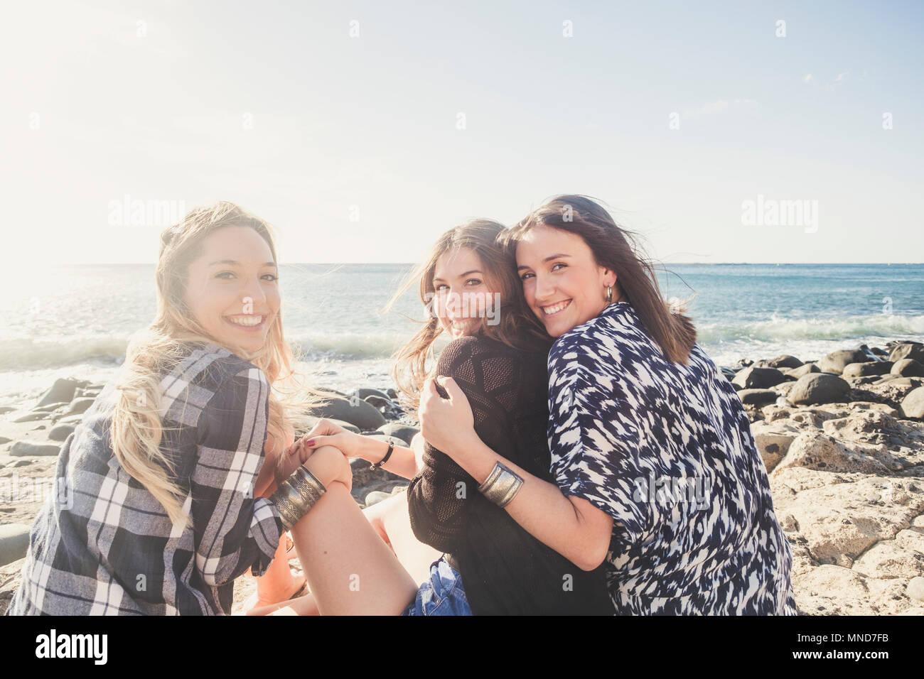 Grupo de mujer hermosa joven hablando y sonriendo aroud en una playa de piedra en la isla de Tenerife. El equipo de chicas que se divierten juntos Imagen De Stock