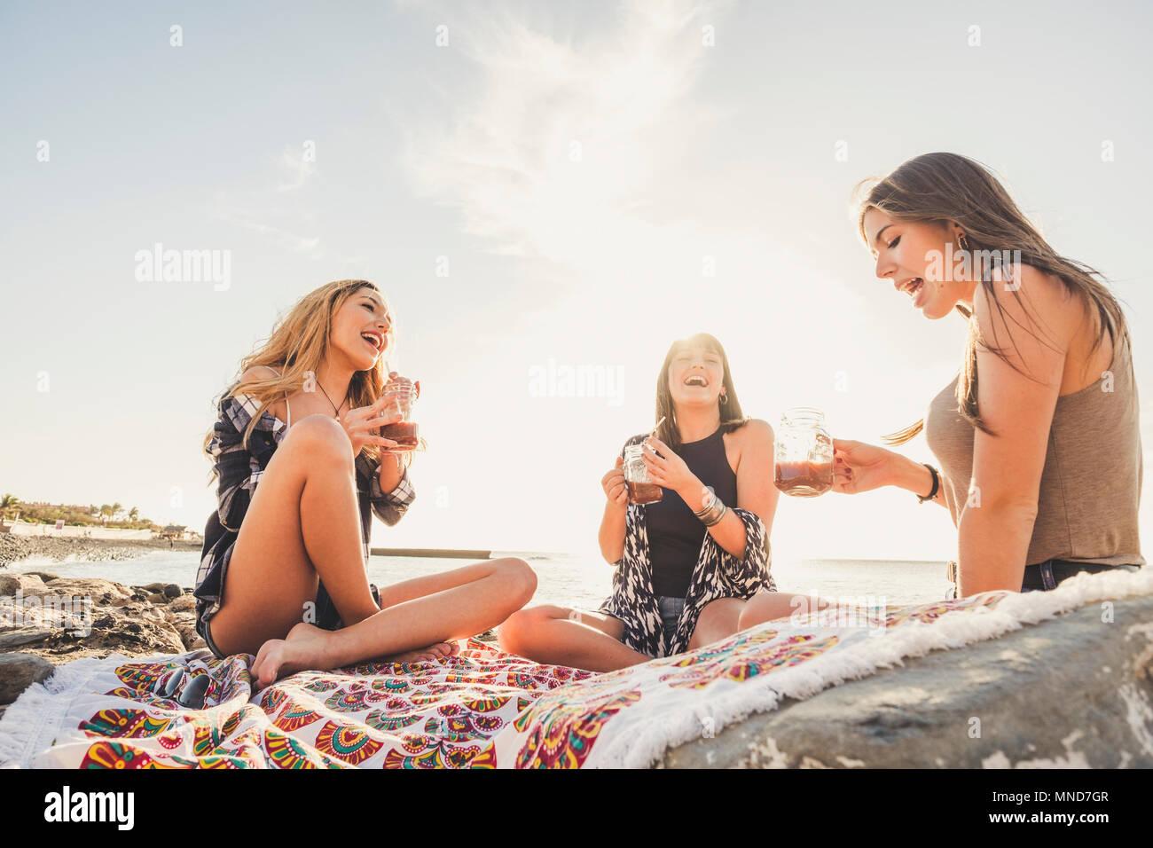 Grupo de mujeres jóvenes amigo bebiendo juntos un jugo de fruta en una roca de Playa en Tenerife. Relación para un equipo ejoy las vacaciones y la felicidad. Imagen De Stock