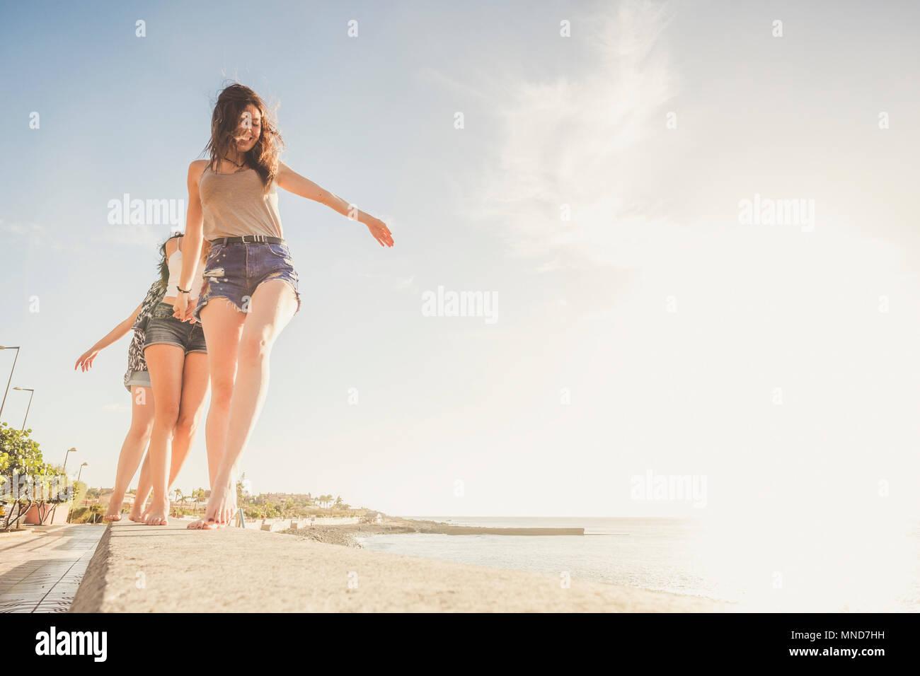 Tres jóvenes amigos, caminar juntos en una pared cerca de la Playa en Tenerife. Disfrute de las mejores vacaciones bajo un cielo azul con sol amarillo. Las manos con las manos. Foto de stock