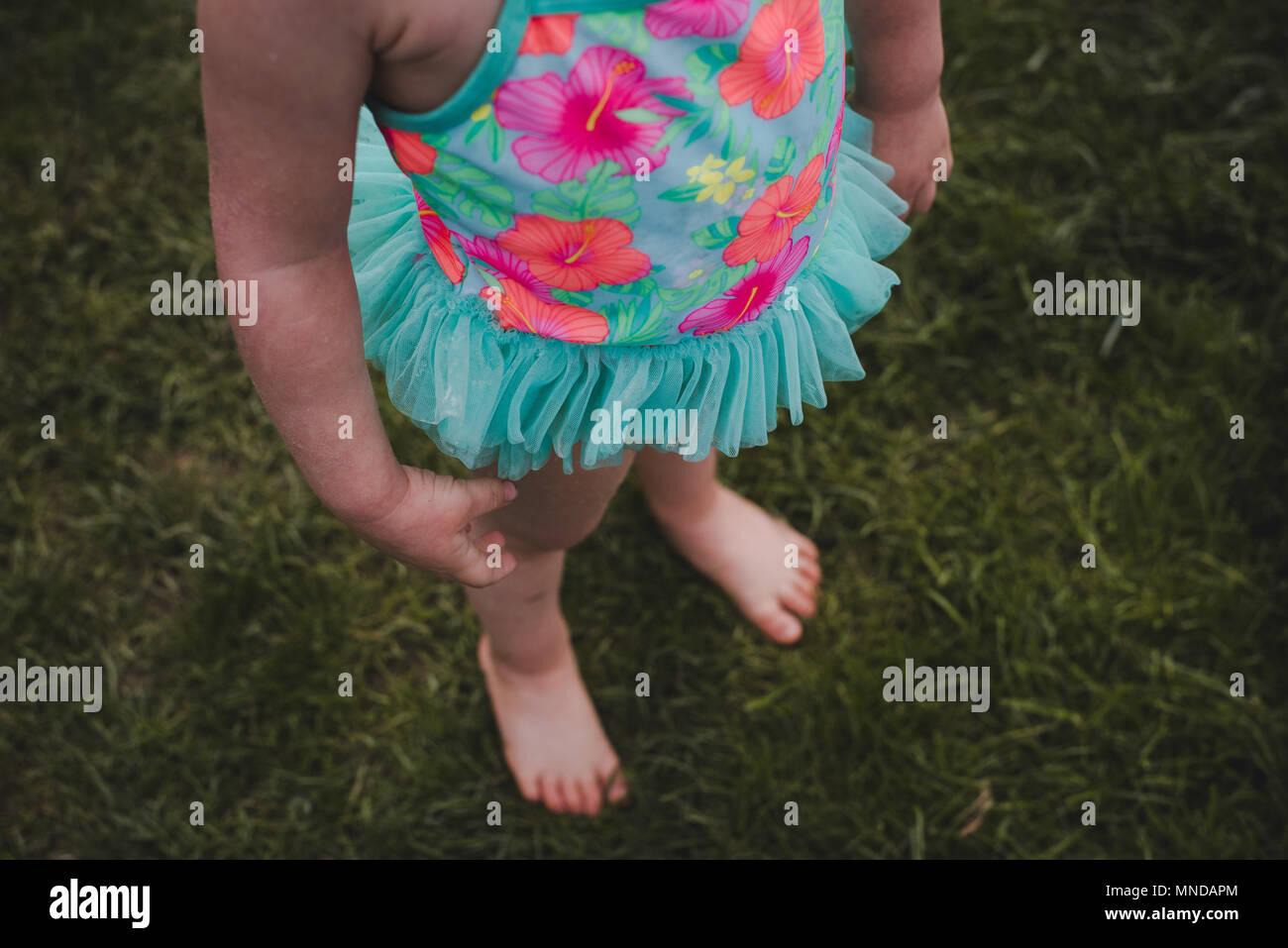 Un niño sin rostro vestida de un traje de baño de color brillante con flores sobre ella. Foto de stock