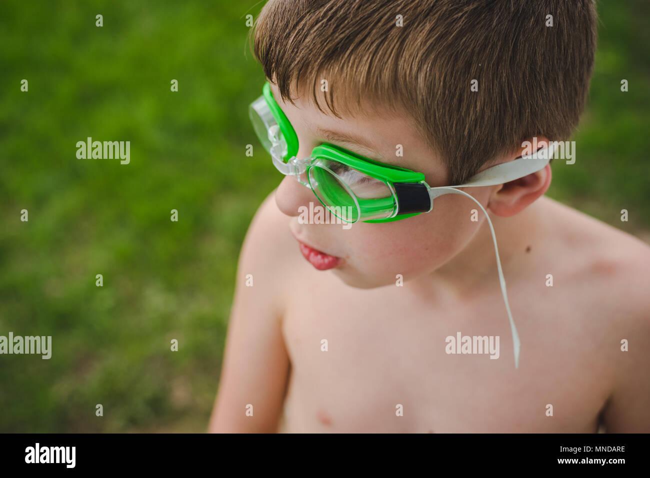 Un niño usando gafas de natación verde en un día soleado de verano Imagen De Stock
