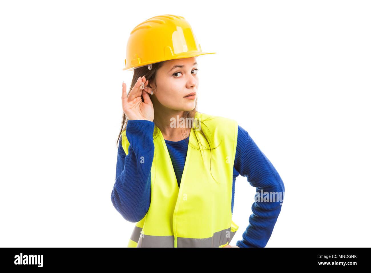 Joven ingeniero atractivo femenino haciendo oír gesto tocando su oreja como prestando atención a los chismes concepto aislado sobre fondo blanco. Imagen De Stock