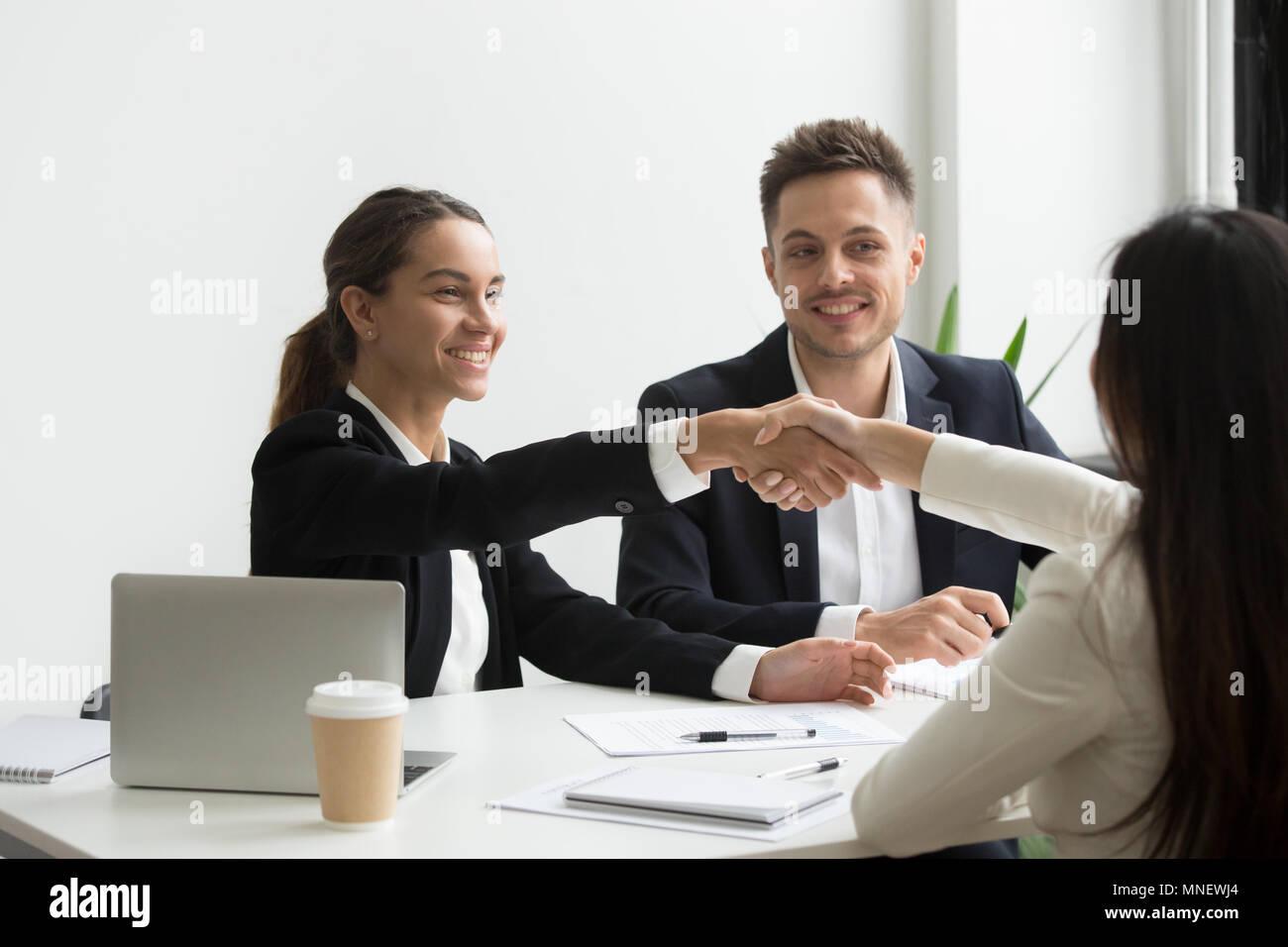 Representantes HR positivamente saludo candidato al trabajo femenino Foto de stock