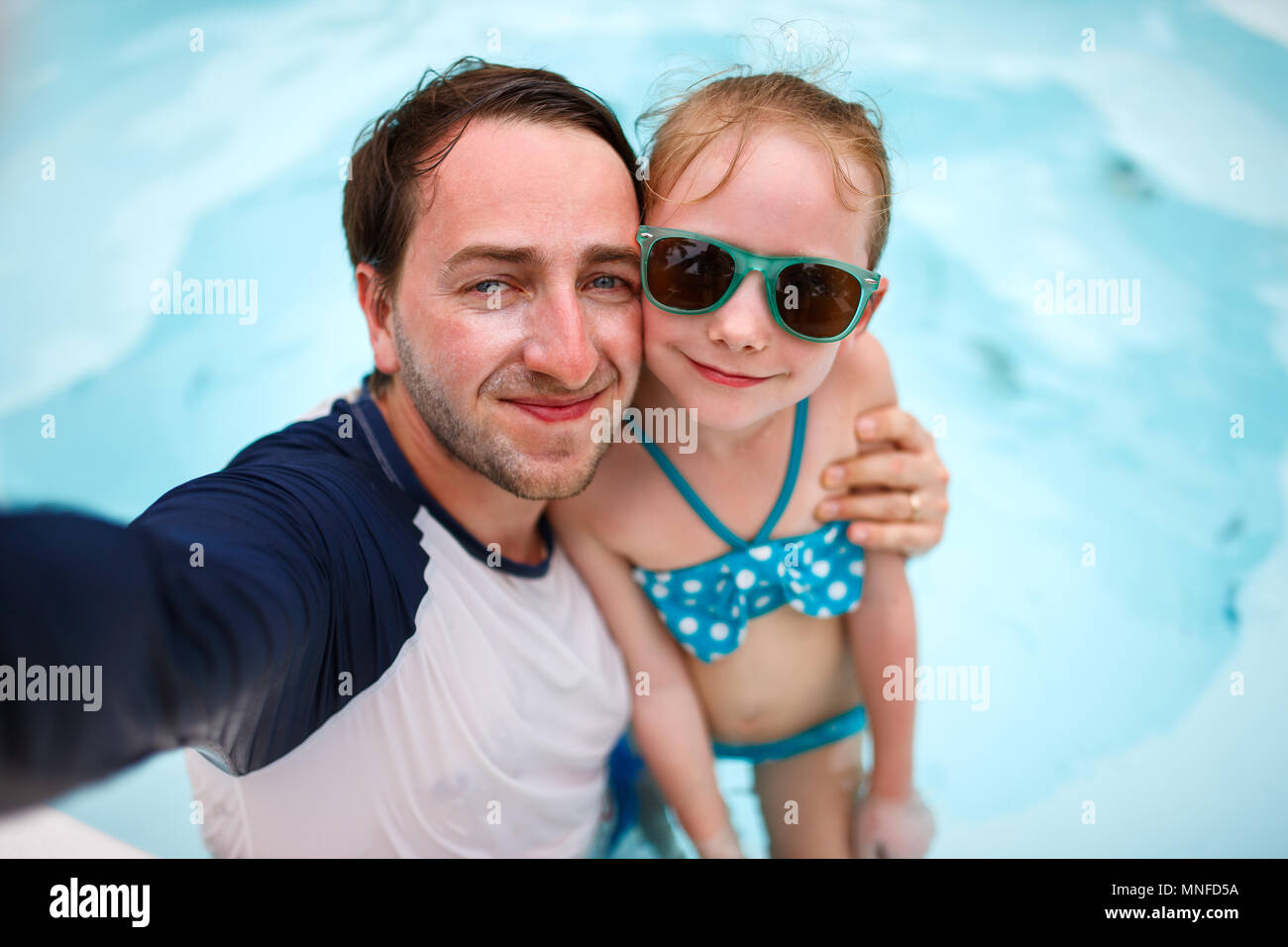 Padre de familia feliz y su adorable hija pequeña en una piscina al aire libre haciendo selfie Imagen De Stock