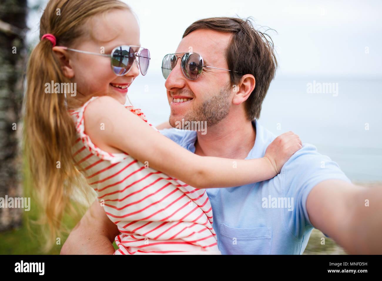 Padre de familia feliz y su adorable hija pequeña en la playa, haciendo selfie Imagen De Stock