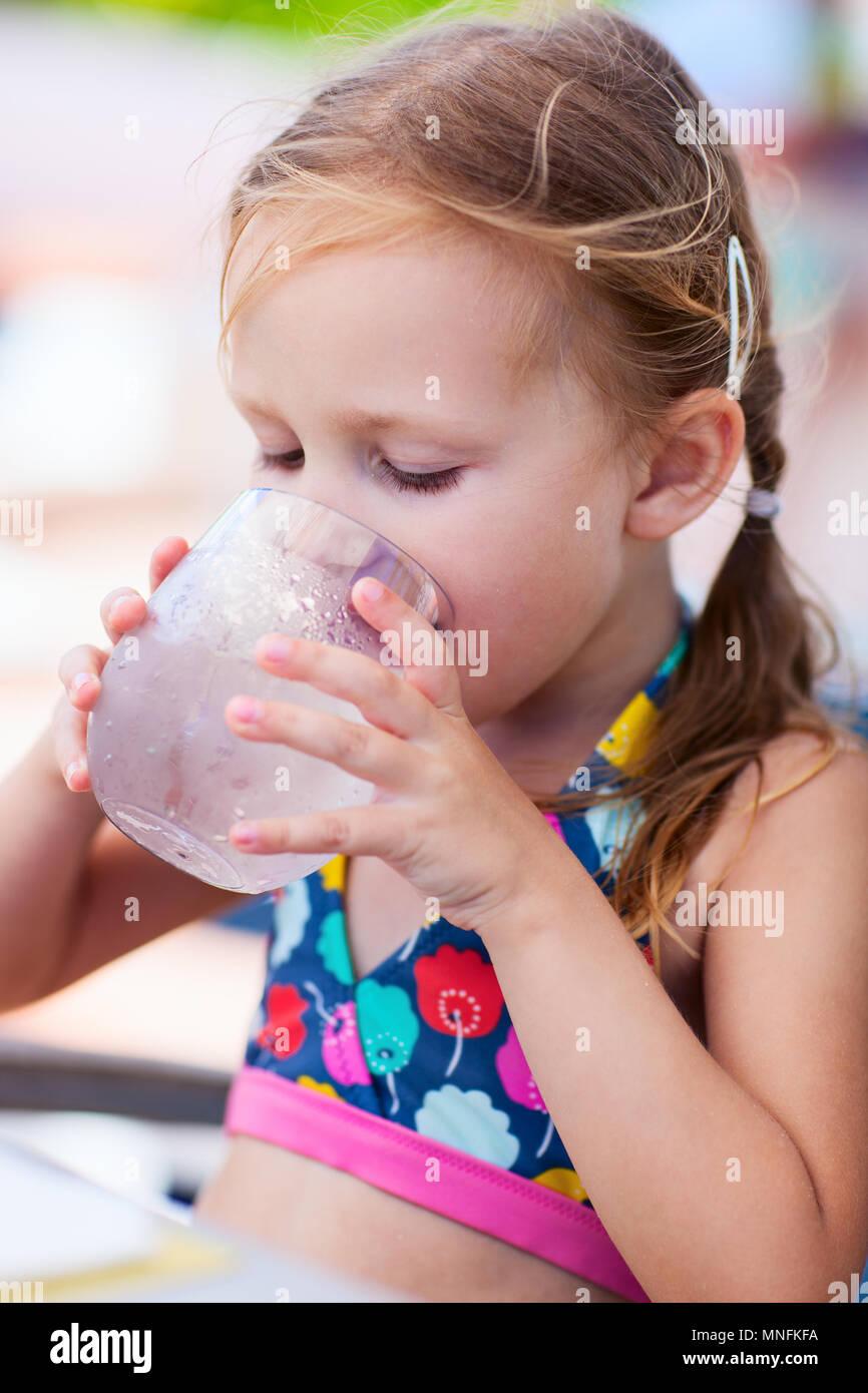 Adorable niña en un vaso de agua potable Imagen De Stock