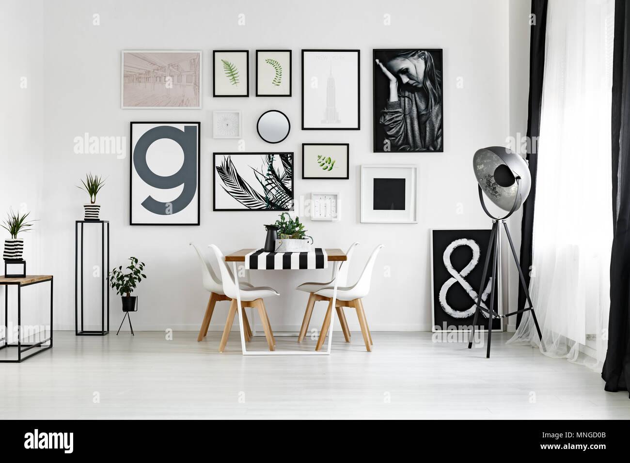 Mesa de comedor por la pared blanca con carteles en el espacioso salón Foto de stock