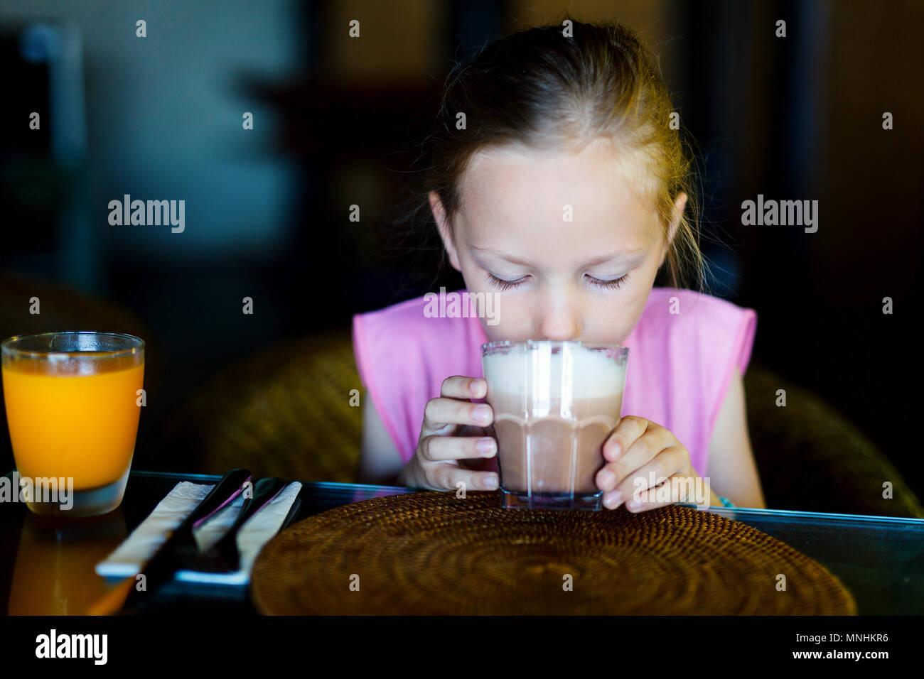 Adorable niña en el restaurante bebiendo chocolate Foto de stock