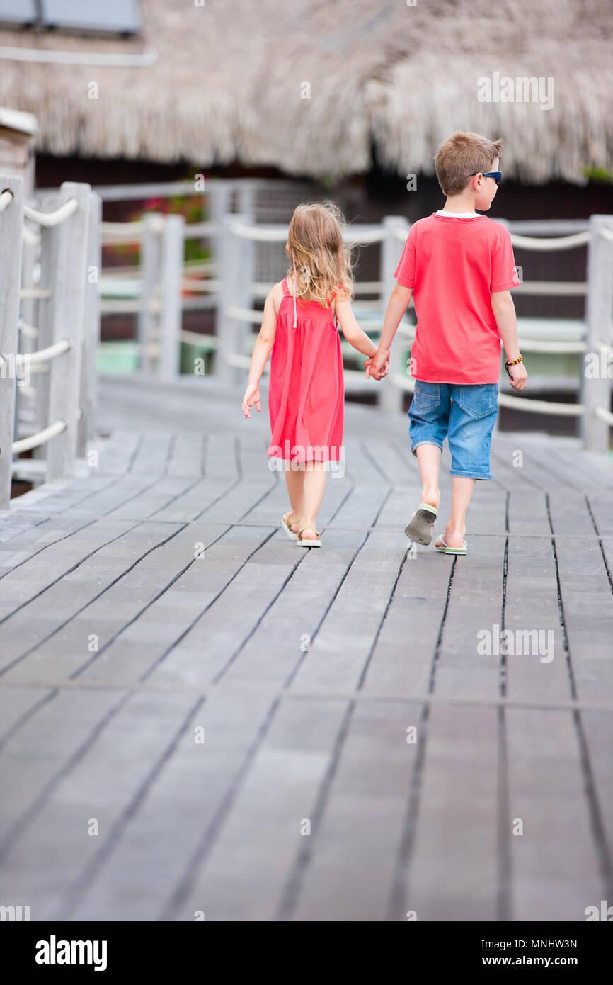 Vista posterior de dos niños caminando hacia bungalows sobre el agua Imagen De Stock