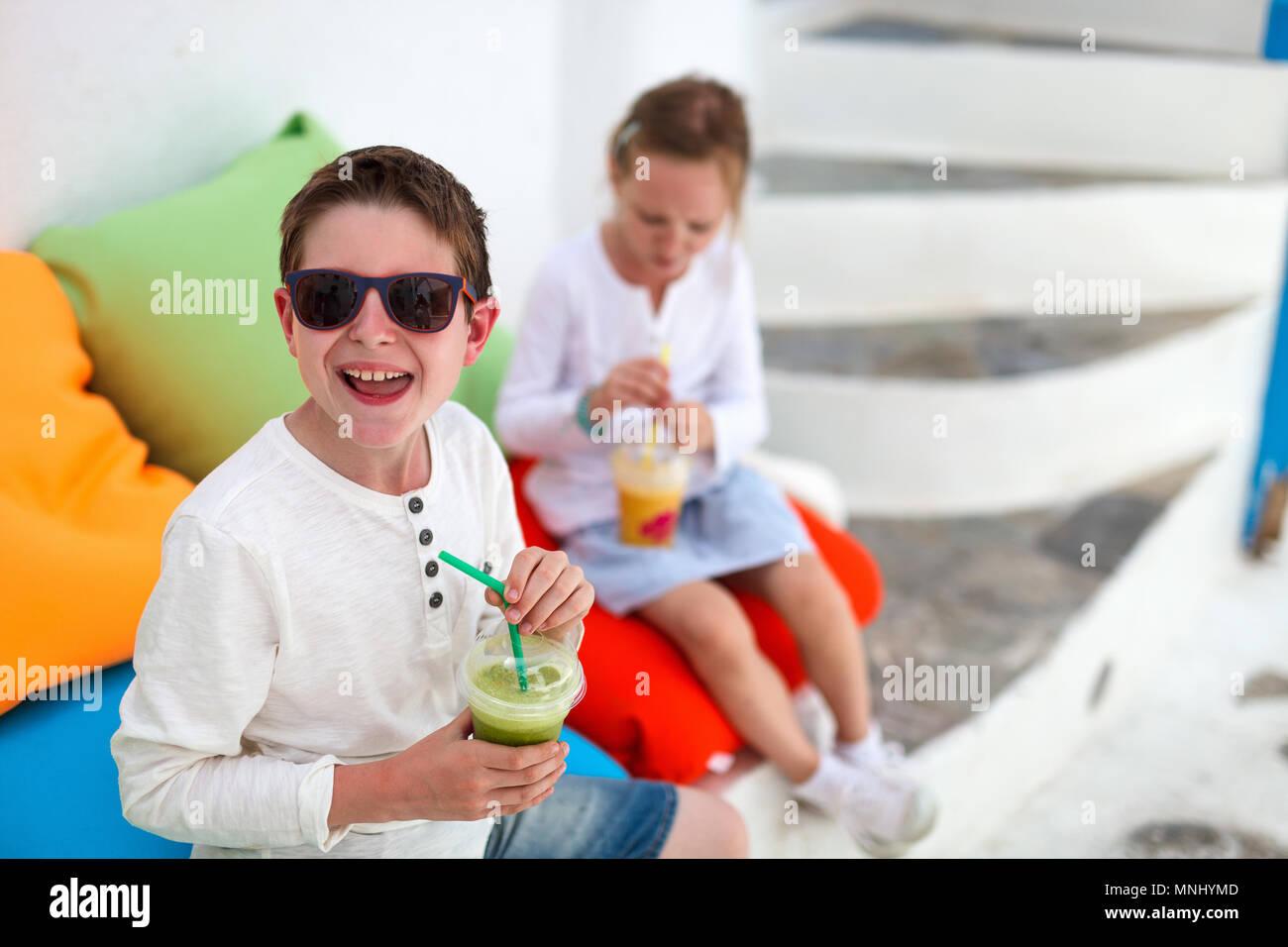 Dos lindos hijos hermano y hermana de beber batidos fresco en un colorido almohadas en la cafetería al aire libre en verano Imagen De Stock