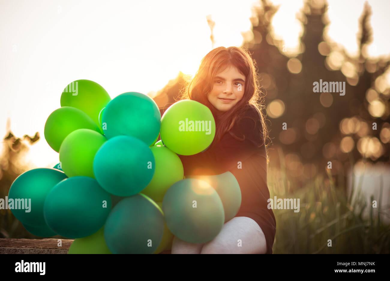 Retrato de una bonita niña sentada en el parque con el montón de globos de aire verde suave al aire libre en la luz del sol por la noche, celebrando un cumpleaños, preparati Imagen De Stock