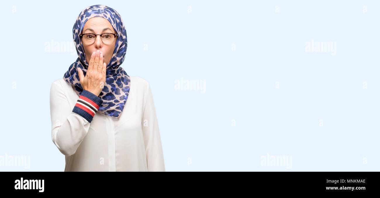 Edad media los árabes musulmanes mujer vistiendo el hijab cubre boca en estado de shock, parece tímido, expresando el silencio y confundir los conceptos, asustada aislados de fondo azul Foto de stock