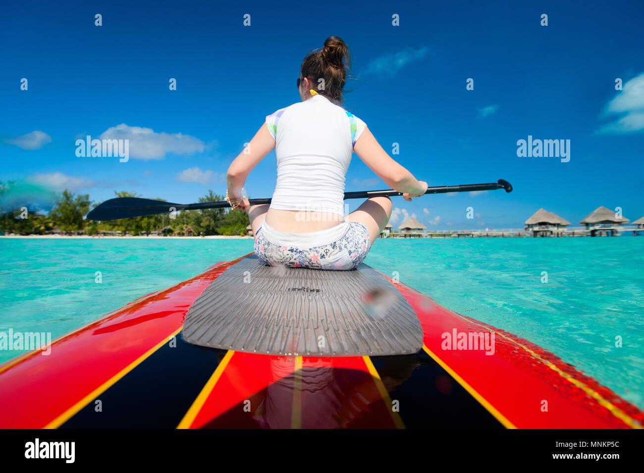 Vista posterior de la joven mujer deportiva en paddle board Foto de stock