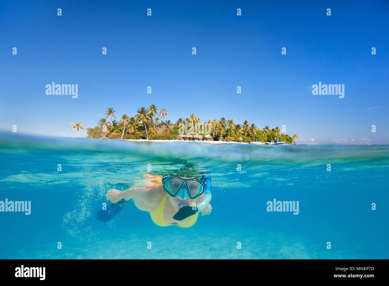 Mujer snorkeling en aguas claras tropicales delante de exótica isla Foto de stock