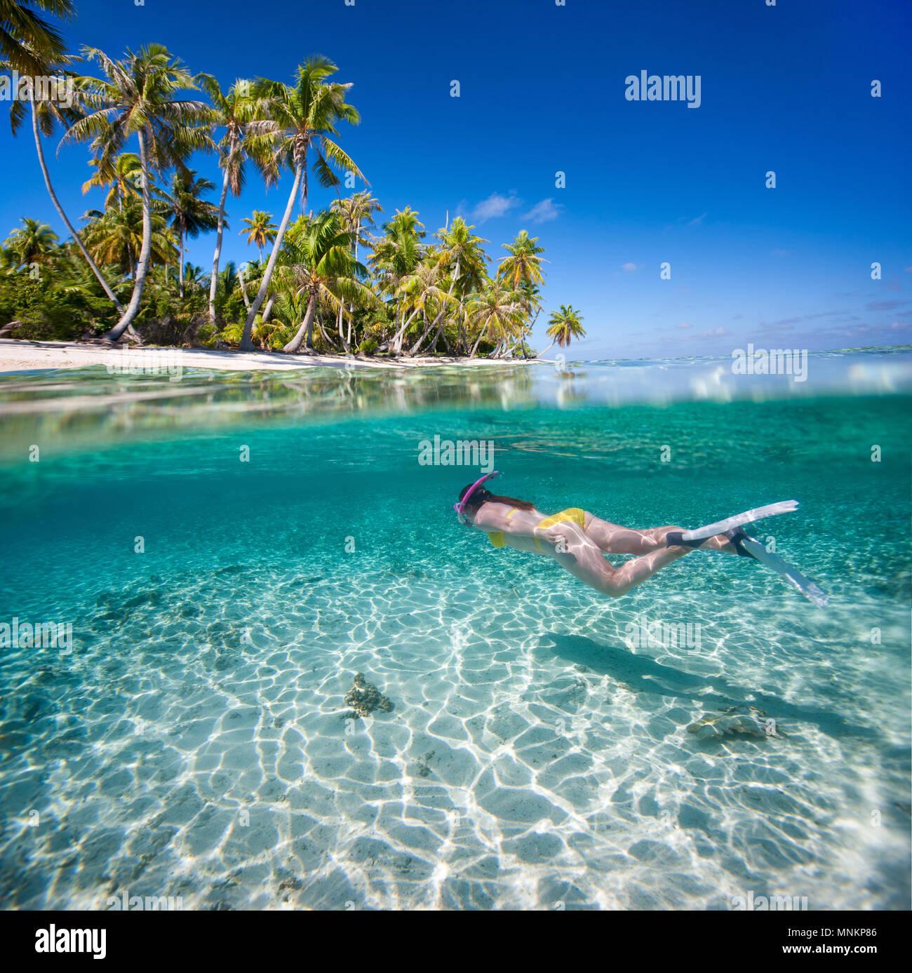 Mujer nadar en aguas claras tropicales delante de exótica isla Foto de stock